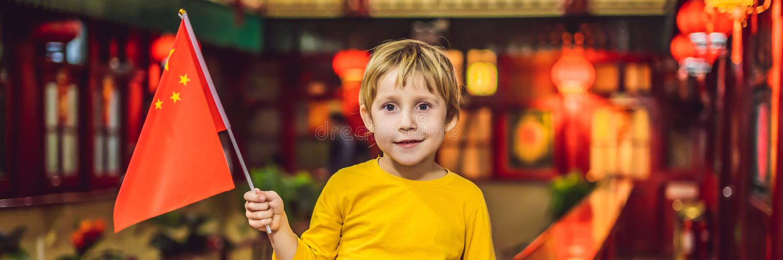 Enjoying vacation in China. Happy tourist boy with a Chinese flag on a Chinese background. Travel to China with kids stock photos