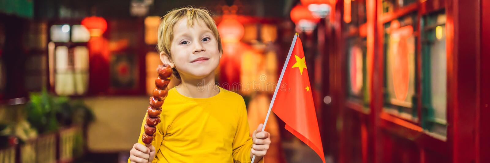 Enjoying vacation in China. Happy tourist boy with a Chinese flag and with traditional Chinese candied fruits on a stock image