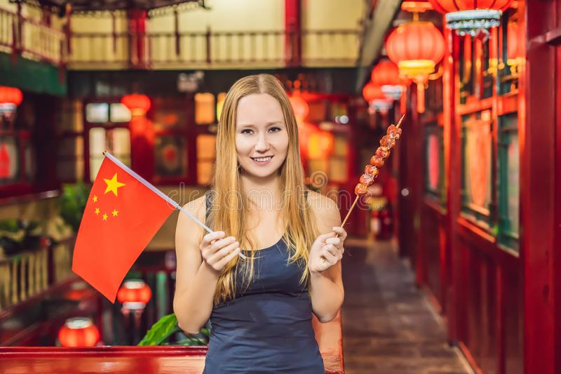 Enjoying vacation in China. Happy woman tourist with a Chinese flag and with traditional Chinese candied fruits on a stock images