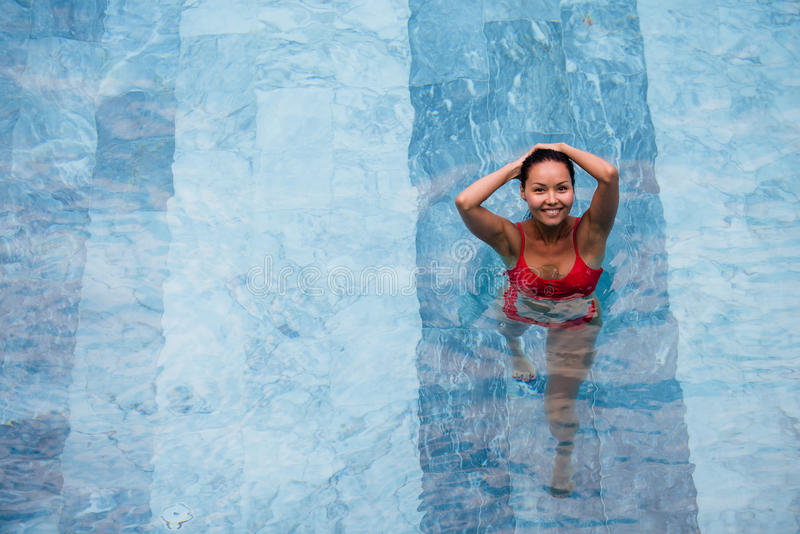 Enjoying vacation. Smiling beautiful young woman in swimming pool. stock image