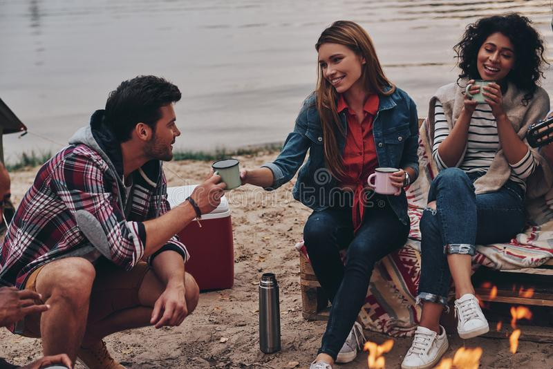 Enjoying warm tea. Group of young people in casual wear smiling and holding mugs while camping near the bonfire stock photos