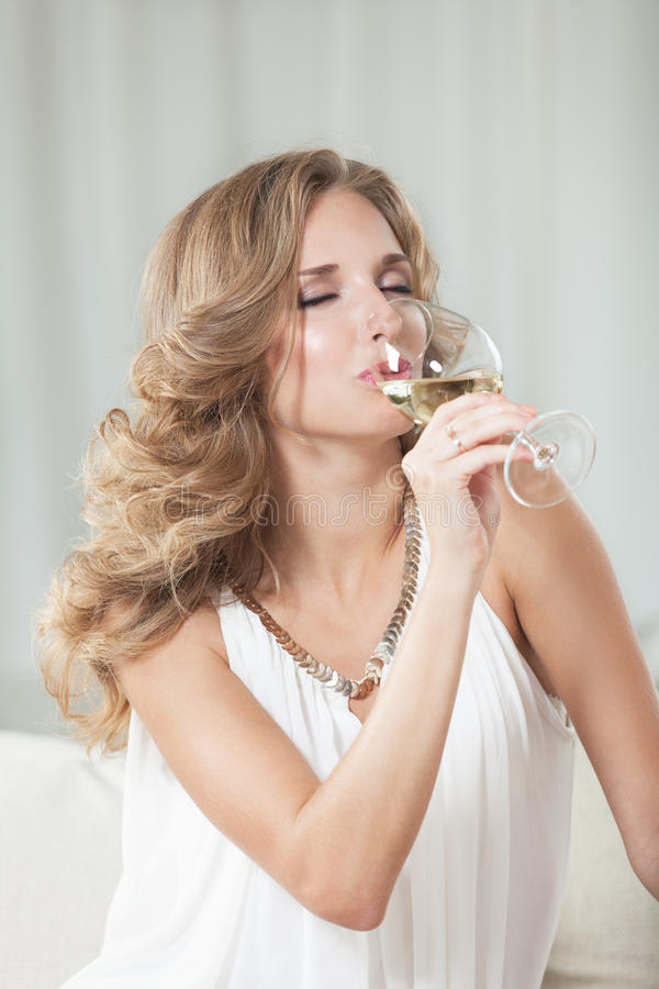 Enjoying wine. Attractive girl enjoying white wine in the restaurant royalty free stock image