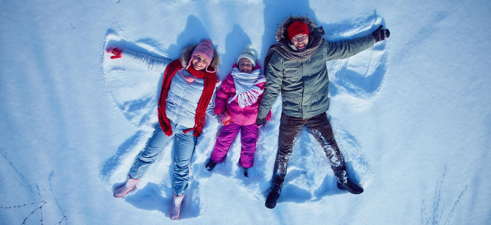 Enjoying winter day. Young couple and little girl looking at camera while lying in snowdrift stock photos