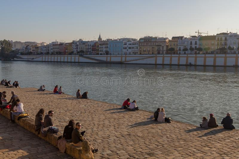 Enjoying the winter sun along the Guadalquivir banks in Seville. Sevilla, Andalusia / Spain - 01-03/2019 People enjoying their free time in the historic city stock photography