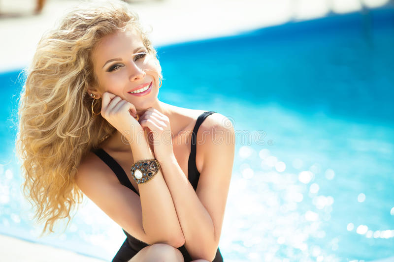 Enjoyment. beautiful happy smiling woman with blond hair relaxing beside a swimming pool. Summer outdoor portrait. stock photos