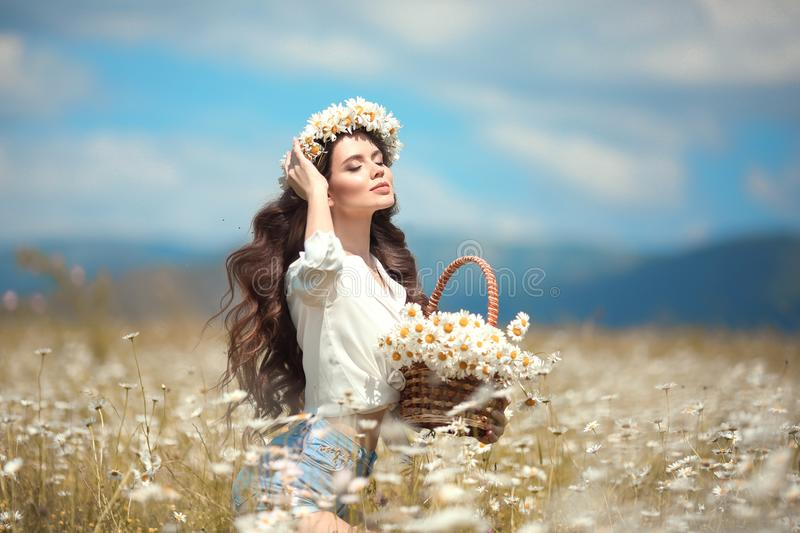 Enjoyment. Beautiful young girl with basket of flowers over chamomile field. Carefree happy brunette woman with healthy wavy hair royalty free stock photos