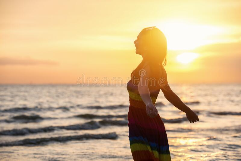 Enjoyment - free happy woman enjoying sunset. Beautiful woman in white dress embracing the golden sunshine glow of sunset with arms outspread and face raised stock photos