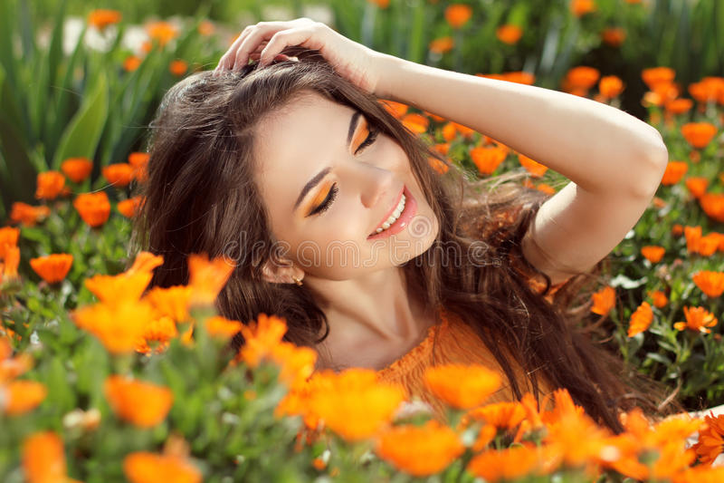 Enjoyment - free smiling woman enjoying happiness. Beautiful woman embracing in golden marigold flowers royalty free stock photos