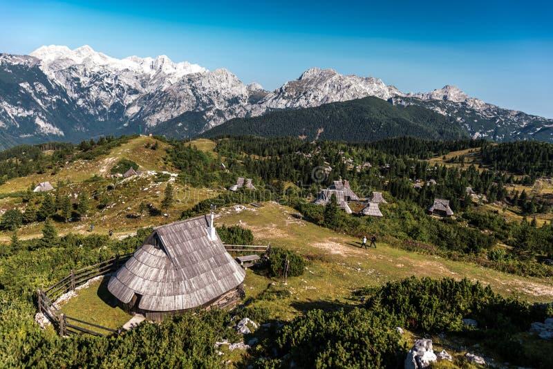 Enjoyng η άποψη της πράσινης χλόης και hutts σχετικά με το planina velika στοκ εικόνες