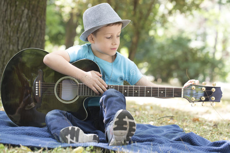 He really enjoys while playing guitar stock images