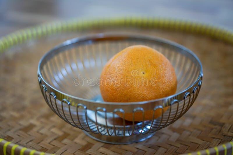 Enkel apelsin i metallkorg på träsicksackplattan arkivbilder