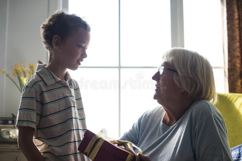 Enkel, der seiner Großmutter ein Geschenk gibt lizenzfreie stockfotografie