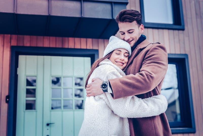 Enkel echtpaar koesteren die zich buiten hun nieuw huis bevinden stock fotografie