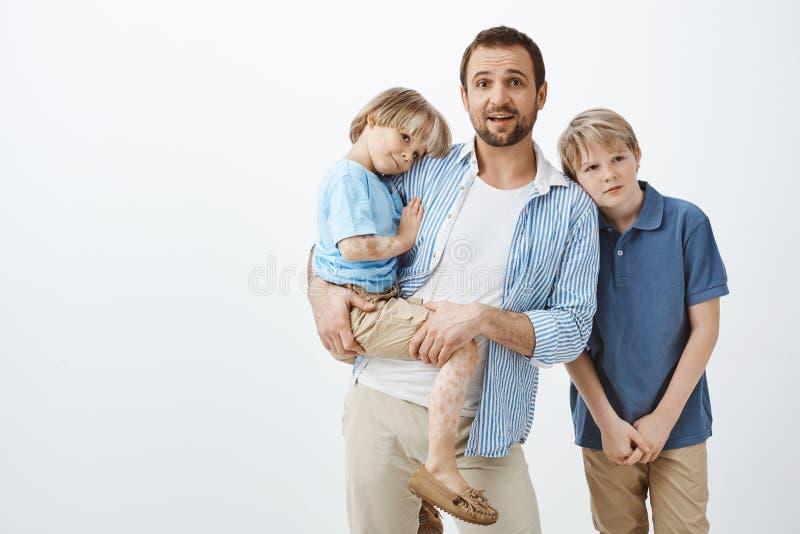 Enkel förälder som sköter söner Farsa som rymmer det gulliga barnet med vitiligo, medan stirra nervöst på kameran, lämnas arkivfoton