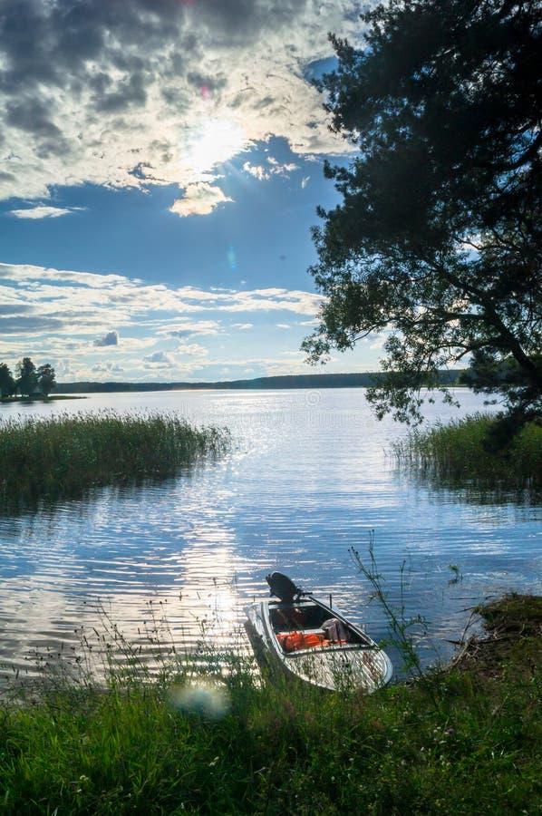 Enkel fishers`-motorbåt som förtöjas till den strand- skogen av sjön Seliger under det bländande solljuset, Ryssland arkivfoto