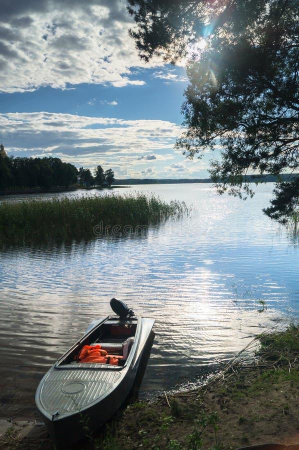 Enkel fishers`-motorbåt som förtöjas till kusten och sikten av utrymmena av sjön Seliger under det bländande solljuset, Ryssland royaltyfria bilder
