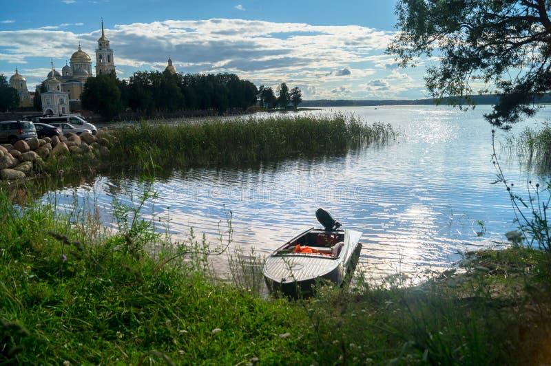 Enkel fishers`-motorbåt som förtöjas till kusten och sikten av utrymmena av sjön Seliger under det bländande solljuset, Ryssland arkivbilder
