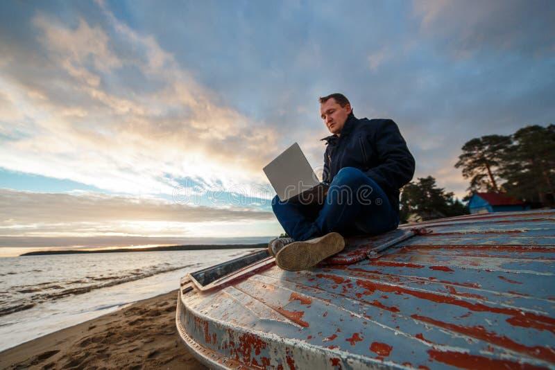 Enkel freelancer som arbetar genom att använda bärbara datorn i fartyget på havsstranden royaltyfria bilder