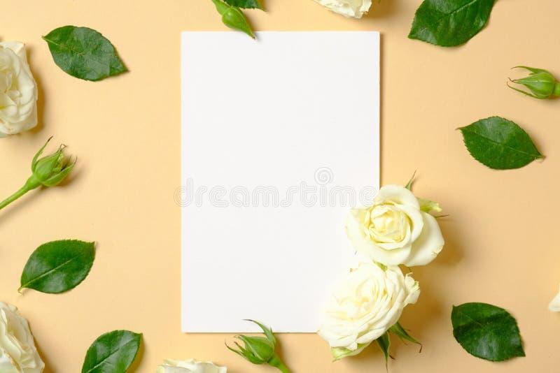 enkel Geregend Witte bloemen en groene bladeren op pastelkleur gele achtergrond Vlak leg, hoogste mening, exemplaarruimte Creatie stock foto