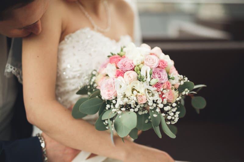 Enkel het gehuwde huwelijkspaar stellen en bruidholding in handenboeket royalty-vrije stock afbeelding