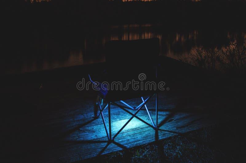 Enkel isolerad stol på en träyttersida med blått ljus under arkivfoto