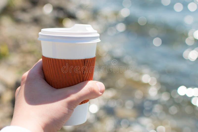 Enkel kopp för kaffe i hand på bakgrunden av sjön i bokeh arkivbild
