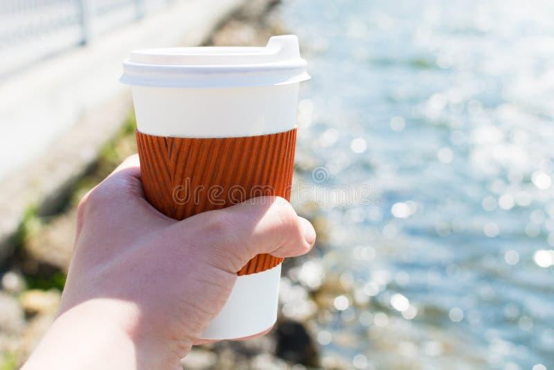 Enkel kopp för kaffe i hand på bakgrunden av sjön i bokeh fotografering för bildbyråer
