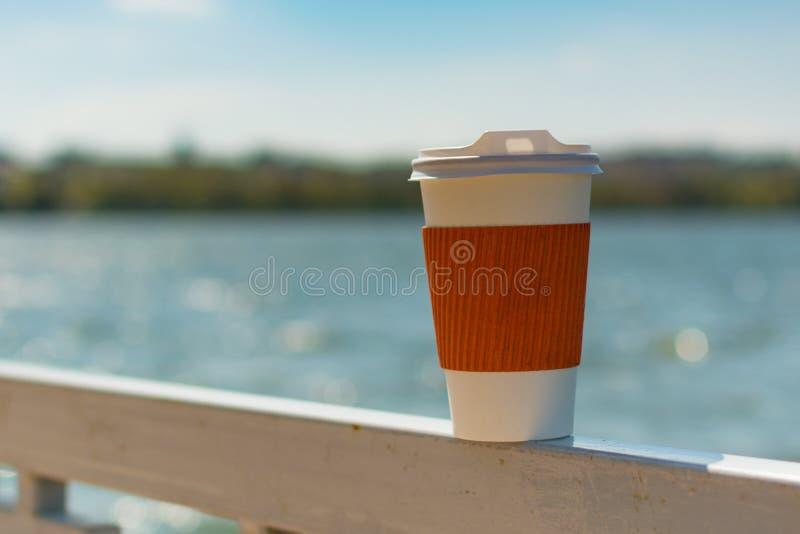 Enkel kopp för kaffe på bakgrunden av sjön och staden i bokeh royaltyfri foto