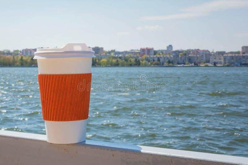 Enkel kopp för kaffe på bakgrunden av sjön och staden i bokeh arkivbild