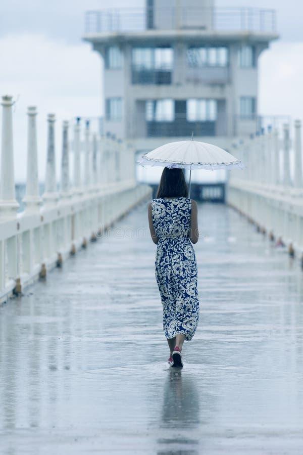 Enkel kvinna som går på väg med att tappa för paraply och för regn royaltyfri fotografi