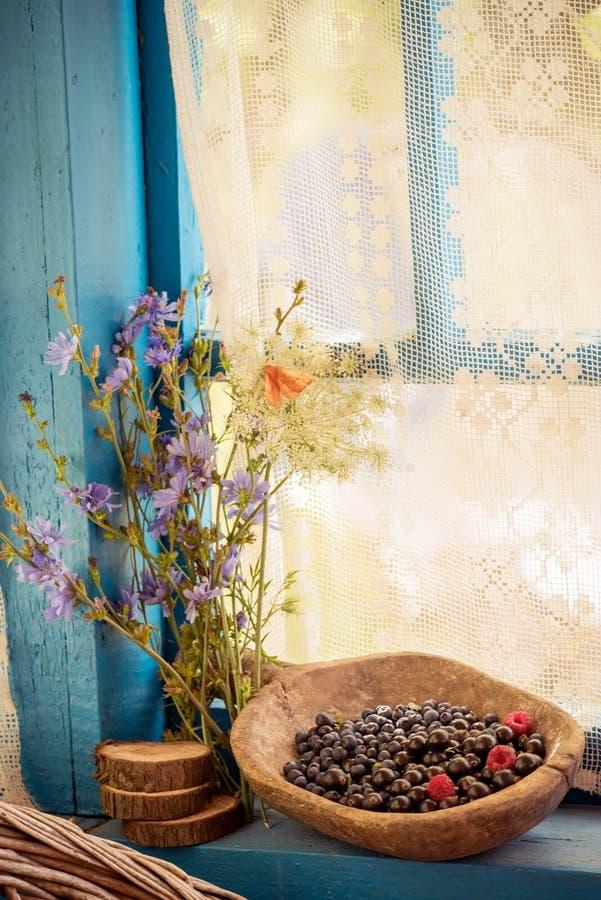 Enkel lantlig stilleben Lösa bär i en trägammal maträtt och lösa blommor atmosfär för sommarferie i bygden royaltyfri fotografi