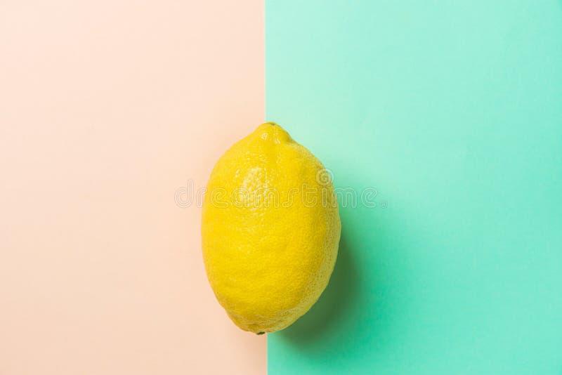 Enkel ljus mogen gul citron på kontrastbakgrund från kombination av rosa Peachy turkosbakgrund Utformad idérik bild royaltyfria foton