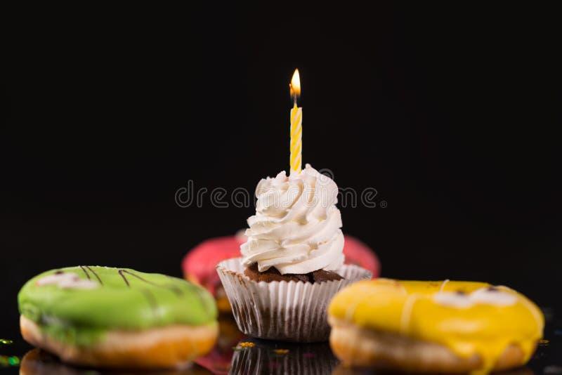 Enkel med is muffin med födelsedagstearinljuset royaltyfria foton