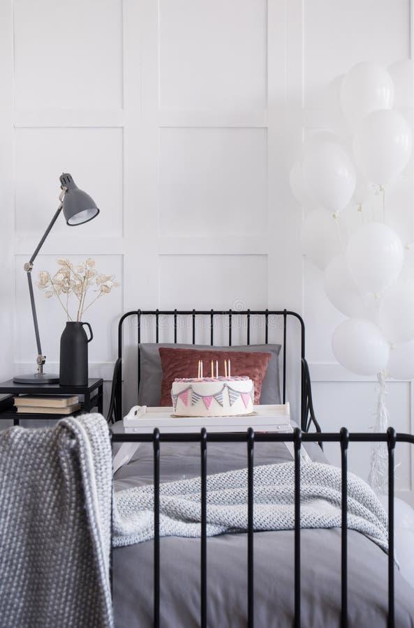 Enkel metallsäng med grå sängkläder och burgundy kudde, födelsedagkaka med stearinljus på den vita treyen, verkligt foto med royaltyfria foton
