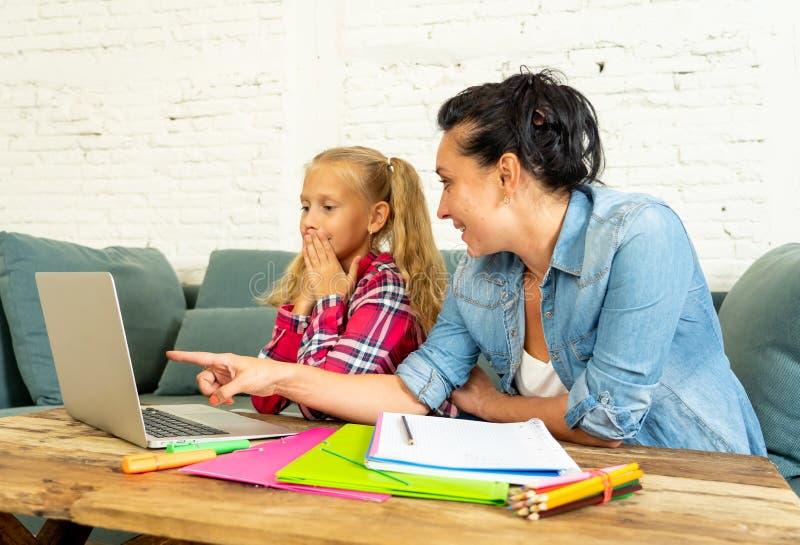 Enkel mum som hjälper hennes dotter som gör hennes läxa med den hemmastadda bärbara datorn royaltyfria bilder