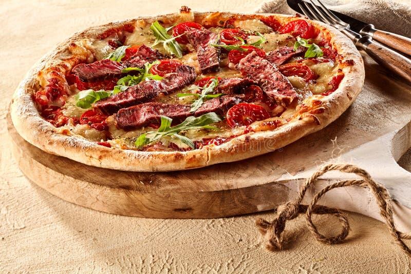 Enkel portion av smaklig nötkött- och arugulapizza arkivfoto