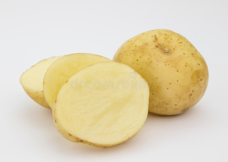 Enkel potatis och en som skivas på vit royaltyfri bild