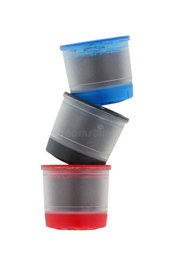 Enkel servekaffekapslar i blått, svart och rött som isoleras på arkivbild