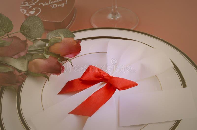Enkel ställeinställning för valentin dag med det svartvita porslinet, siden- röda rosor, en pilbåge på en röd bakgrund royaltyfri bild