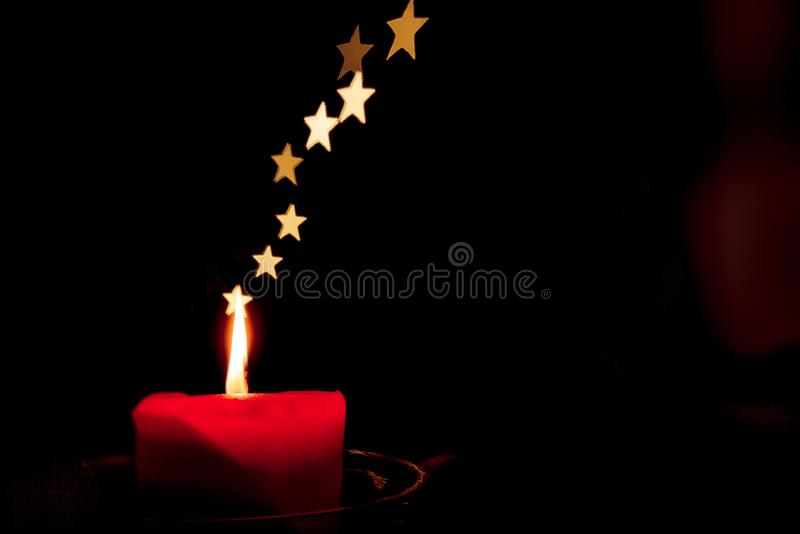 Enkel stearinljus i mörkret med stjärnor i stället för rök arkivbild