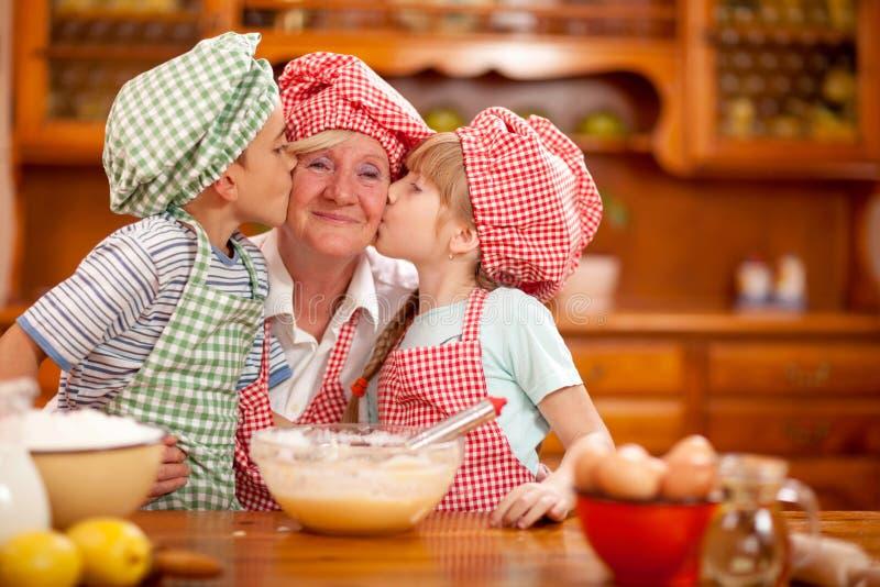 Enkel und Enkelin küssen ihre Großmutter in der Küche stockbild