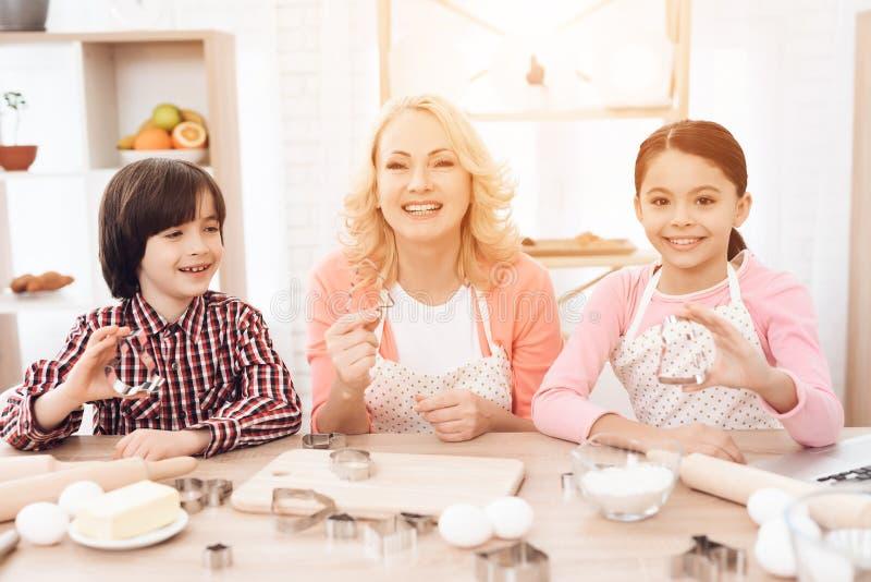 Enkel und Enkelin zusammen mit glücklicher Großmutter nehmen an dem Kochen in der Küche teil stockfotos