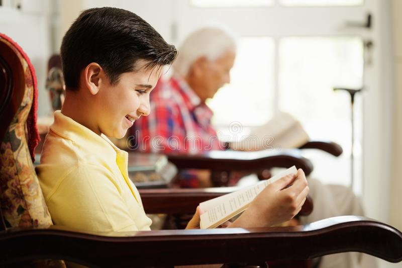 Enkel-und Großvater-Lesebuch und zu Hause sich entspannen stockfotografie