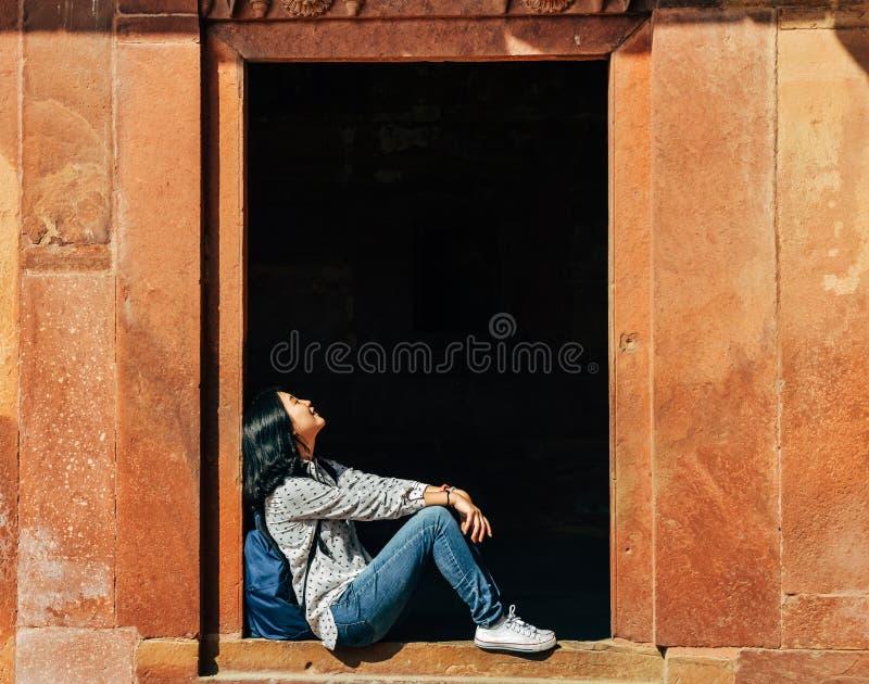 Enkel ung kvinna som vilar på tröskeln på Fatehpur Sikri, Indien royaltyfria foton
