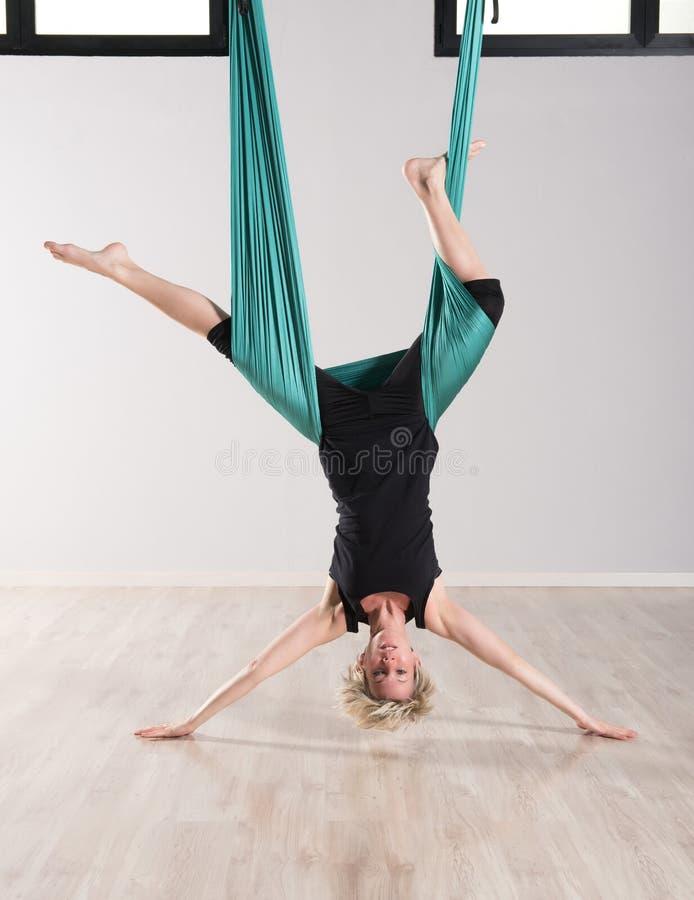 Enkel uppochnervänd kvinna som gör flyg- yoga royaltyfri foto