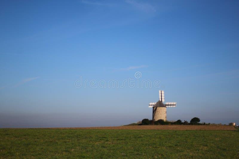 Enkel väderkvarn i mitt av ett grönt fält arkivfoto