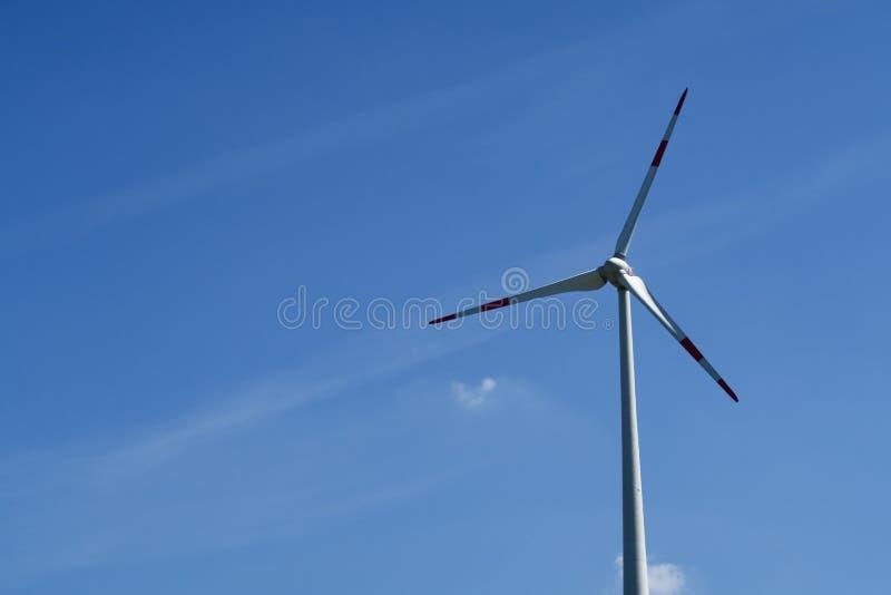 Enkel vindturbin mot en blå himmel arkivbilder