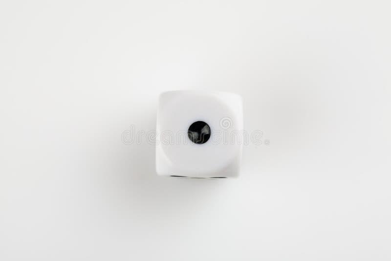 Enkel vit med svart pricktärning på en vit bakgrund som visar nummer ett royaltyfri foto