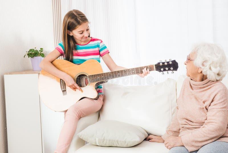 Enkelin, die auf Gitarre für Großmutter spielt lizenzfreie stockfotos