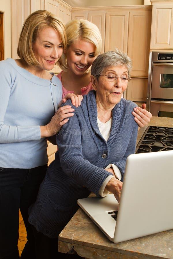 Enkelin, die ihrer Großmutter auf dem Computer hilft lizenzfreie stockbilder